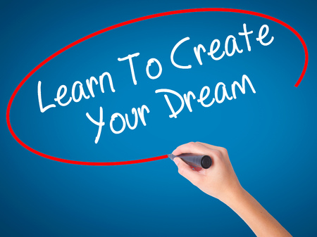 Women Hand writing Learn To Create Your Dream with black marker on visual screen. Isolated on blue. Business, technology, internet concept. Stock Photo