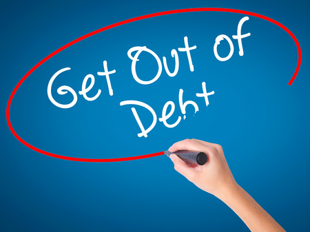 Women Hand writing Get Out of Debt with black marker on visual screen. Isolated on blue. Business, technology, internet concept. Stock Image