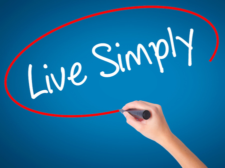 uncomplicated: Women Hand writing Live Simply with black marker on visual screen. Isolated on blue. Business, technology, internet concept. Stock Photo Stock Photo
