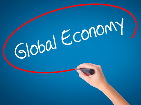 Women Hand writing Global Economy with black marker on visual screen. Isolated on blue. Business, technology, internet concept. Stock Photo