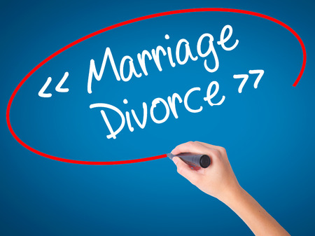 severance: Women Hand writing Marriage - Divorce with black marker on visual screen. Isolated on blue. Business, technology, internet concept. Stock Photo Stock Photo