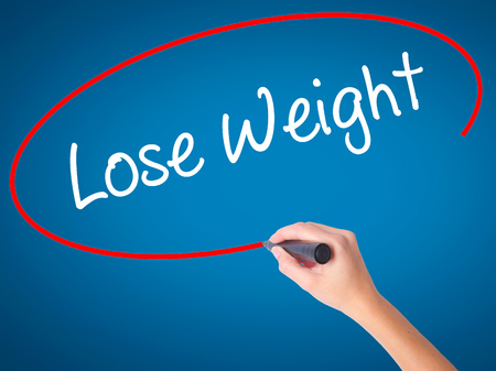 weightloss plan: Women Hand writing Lose Weight with black marker on visual screen. Isolated on blue. Business, technology, internet concept. Stock Photo