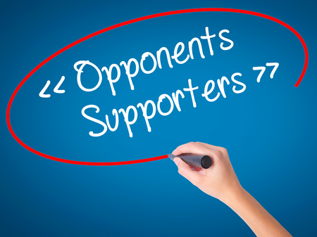 Women Hand writing Opponents - Supporters with black marker on visual screen. Isolated on blue. Business, technology, internet concept. Stock Photo Stock Photo
