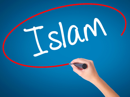 Women Hand writing Islam with black marker on visual screen. Isolated on blue. Business, technology, internet concept. Stock Photo