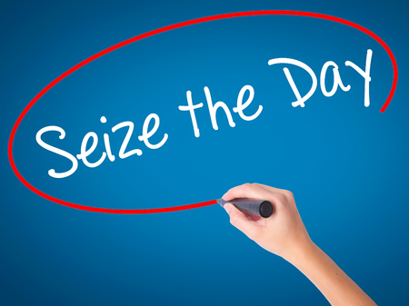 seize: Women Hand writing Seize the Day with black marker on visual screen. Isolated on blue. Business, technology, internet concept. Stock Photo