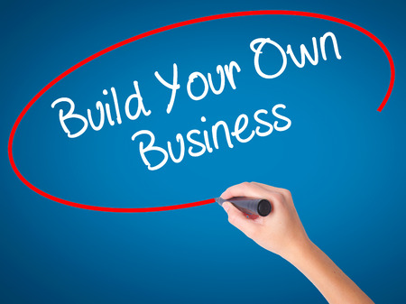 ambitious: Women Hand writing Build Your Own Business with black marker on visual screen. Isolated on blue. Business, technology, internet concept. Stock  Photo Stock Photo