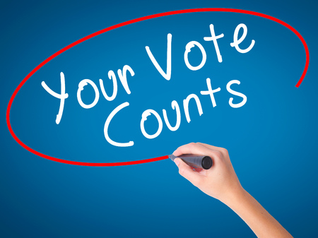counts: Women Hand writing Your Vote Counts with black marker on visual screen. Isolated on blue. Business, technology, internet concept. Stock Image Stock Photo