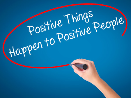 Women Hand writing Positive Things Happen to Positive People with black marker on visual screen. Isolated on blue. Business, technology, internet concept. Stock Photo