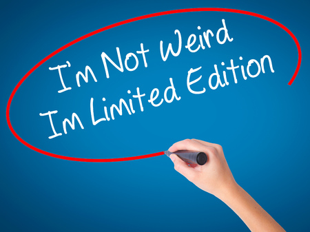 Women Hand writing Im Not Weird Im Limited Edition with black marker on visual screen. Isolated on blue. Business, technology, internet concept. Stock Photo Stock Photo