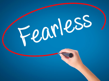 unafraid: Women Hand writing Fearless  with black marker on visual screen. Isolated on blue. Business, technology, internet concept. Stock Photo