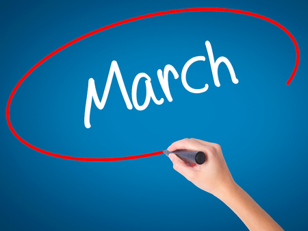 Women Hand writing March with black marker on visual screen. Isolated on blue. Business, technology, internet concept. Stock Photo Stock Photo