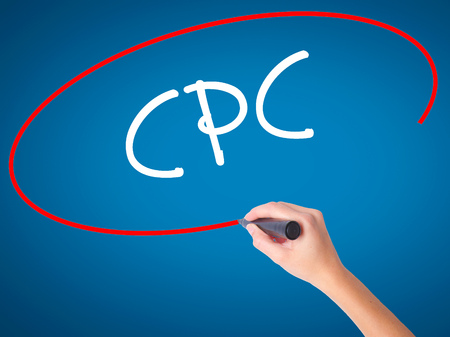 cpc: Women Hand writing CPC (Cost Per Click)  with black marker on visual screen. Isolated on blue. Business, technology, internet concept. Stock Photo