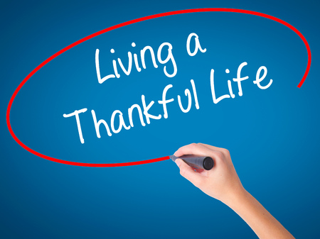 humility: Women Hand writing Living a Thankful Life with black marker on visual screen. Isolated on blue. Business, technology, internet concept.