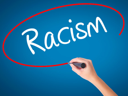 Women Hand writing Racism with black marker on visual screen. Isolated on blue. Business, technology, internet concept. Stock Photo
