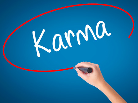 bad fortune: Women Hand writing Karma  with black marker on visual screen. Isolated on blue. Business, technology, internet concept. Stock Photo