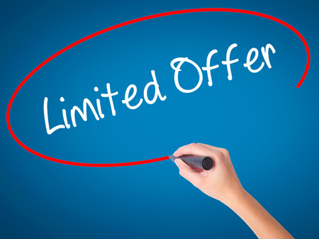 Women Hand writing Limited Offer with black marker on visual screen. Isolated on blue. Business, technology, internet concept. Stock Photo
