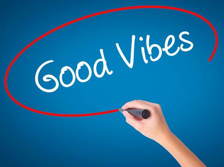 positivismo: Mujeres mano escribiendo Good Vibes con marcador negro en la pantalla visual. Aislado en azul. Negocios, la tecnología, el concepto de internet. Foto de stock Foto de archivo