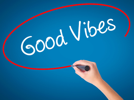positivism: Women Hand writing Good Vibes with black marker on visual screen. Isolated on blue. Business, technology, internet concept. Stock Photo