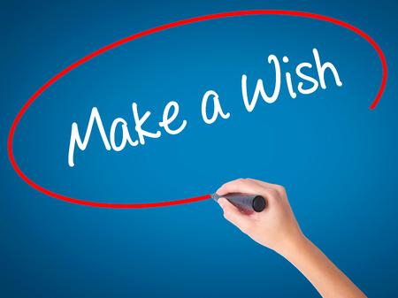 Women Hand writing Make a Wish  with black marker on visual screen. Isolated on blue. Business, technology, internet concept. Stock Photo