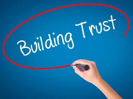 building trust: Women Hand writing Building Trust with black marker on visual screen. Isolated on blue. Business, technology, internet concept. Stock Photo