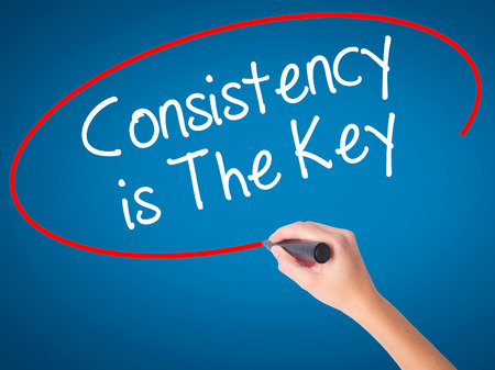 consistency: Women Hand writing Consistency is The Key with black marker on visual screen. Isolated on blue. Business, technology, internet concept. Stock Photo