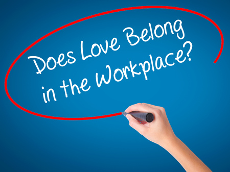 does: Women Hand writing Does Love Belong in the Workplace? with black marker on visual screen. Isolated on blue. Business, technology, internet concept. Stock Photo
