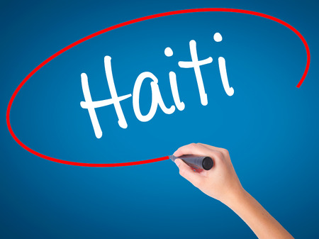 Women Hand writing Haiti with black marker on visual screen. Isolated on blue. Business, technology, internet concept. Stock Photo