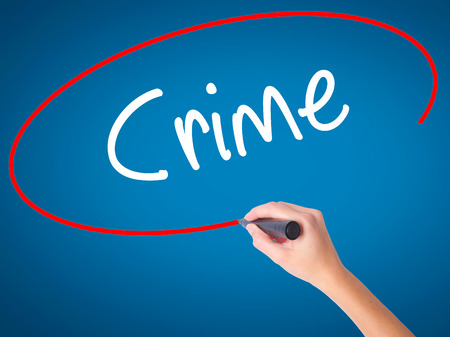 Women Hand writing Crime with black marker on visual screen. Isolated on blue. Business, technology, internet concept. Stock Photo