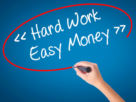 Women Hand writing Hard Work - Easy Money with black marker on visual screen. Isolated on blue. Business, technology, internet concept. Stock Photo
