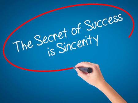 falsehood: Women Hand writing The Secret of Success is Sincerity with black marker on visual screen. Isolated on blue. Business, technology, internet concept. Stock Photo Stock Photo