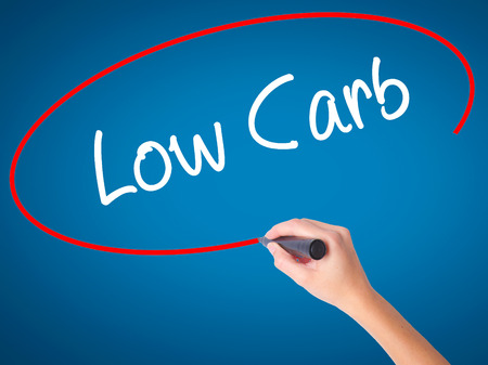 Women Hand writing Low Carb with black marker on visual screen. Isolated on blue. Business, technology, internet concept.