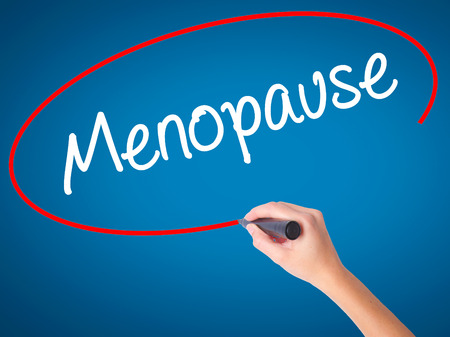 midlife: Women Hand writing Menopause with black marker on visual screen. Isolated on blue. Business, technology, internet concept. Stock Photo Stock Photo