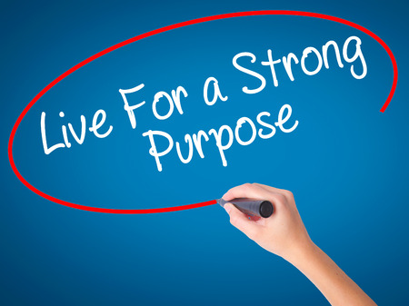 Women Hand writing Live For a Strong Purpose with black marker on visual screen. Isolated on blue. Business, technology, internet concept. Stock Photo