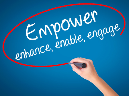 enable: Women Hand writing Empower enhance, enable, engage with black marker on visual screen. Isolated on blue. Business, technology, internet concept. Stock Photo