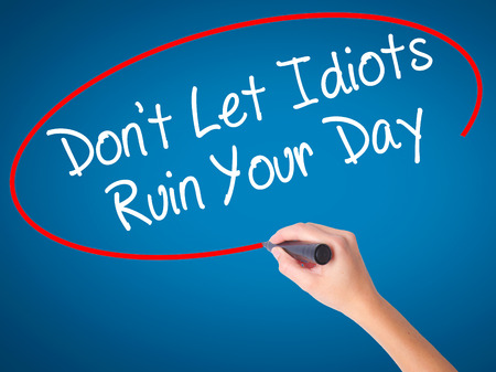 stupidity: Women Hand writing Dont Let Idiots Ruin Your Day with black marker on visual screen. Isolated on blue. Business, technology, internet concept. Stock Photo