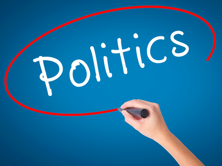 Women Hand writing Politics with black marker on visual screen. Isolated on blue. Business, technology, internet concept. Stock Image