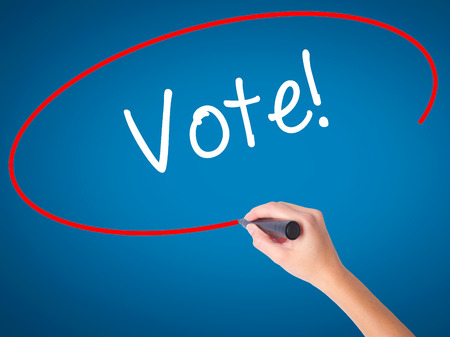 Women Hand writing Vote! with black marker on visual screen. Isolated on blue. Business, technology, internet concept. Stock Photo