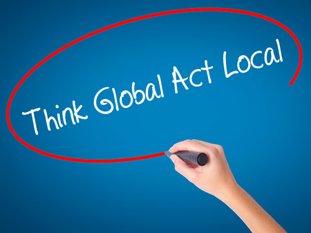 Women Hand writing Think Global Act Local with black marker on visual screen. Isolated on blue. Business, technology, internet concept. Stock Photo