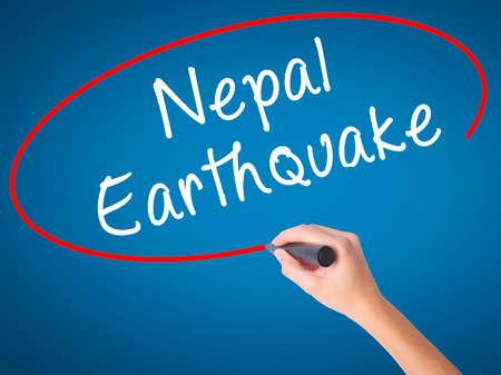 Women Hand writing Nepal Earthquake with black marker on visual screen. Isolated on blue. Business, technology, internet concept. Stock Image