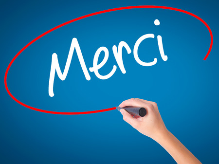 Women Hand writing Merci  (Thank You In French) with black marker on visual screen. Isolated on blue. Business, technology, internet concept. Stock Photo Stock Photo