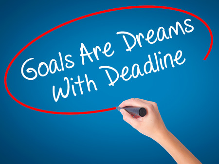 Women Hand writing Goals Are Dreams With Deadline with black marker on visual screen. Isolated on blue. Business, technology, internet concept. Stock Photo