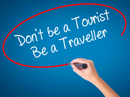 Women Hand writing Dont be a Tourist Be a Traveller  with black marker on visual screen. Isolated on blue. Business, technology, internet concept. Stock Photo Stock Photo