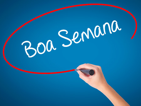 Women Hand writing Boa semana   (Good WeekIn portuguese)with black marker on visual screen. Isolated on blue. Business, technology, internet concept. Stock Photo Stock Photo