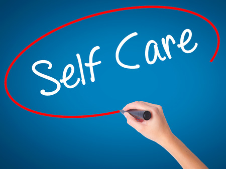 self care: Women Hand writing Self Care with black marker on visual screen. Isolated on blue. Business, technology, internet concept. Stock Photo