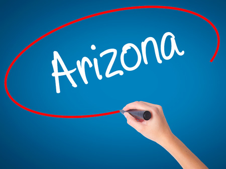 stone of destiny: Women Hand writing  Arizona  with black marker on visual screen. Isolated on blue. Business, technology, internet concept. Stock Photo