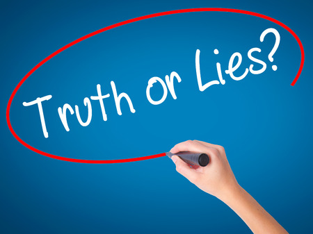 dishonesty: Women Hand writing Truth or Lies? with black marker on visual screen. Isolated on blue. Business, technology, internet concept. Stock Photo Stock Photo