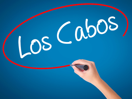 Women Hand writing Los Cabos with black marker on visual screen. Isolated on blue. Business, technology, internet concept. Stock Photo