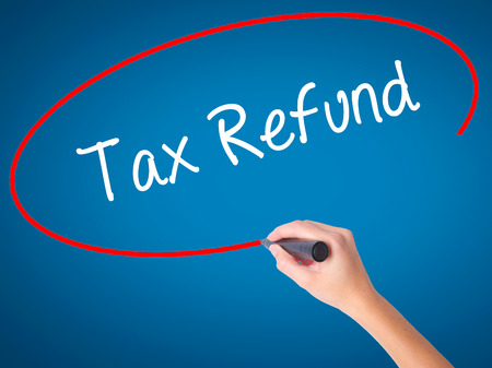 Women Hand writing Tax Refund with black marker on visual screen. Isolated on blue. Business, technology, internet concept. Stock Photo