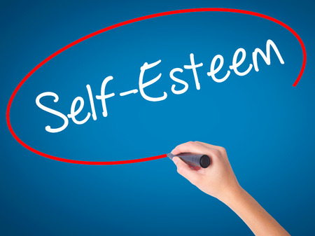 self worth: Women Hand writing Self-Esteem with black marker on visual screen. Isolated on blue. Business, technology, internet concept. Stock Photo