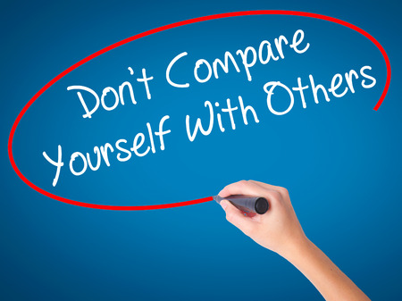 Women Hand writing Dont Compare Yourself With Others with black marker on visual screen. Isolated on blue. Business, technology, internet concept. Stock Photo Stock Photo